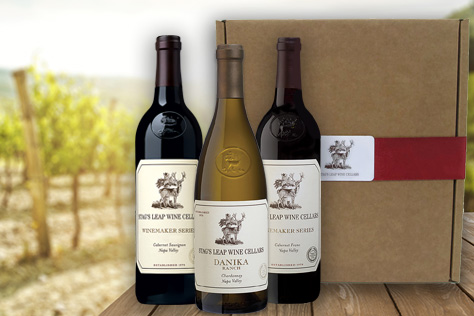 3-bottle box and 3 bottles of wine on a table in a vineyard