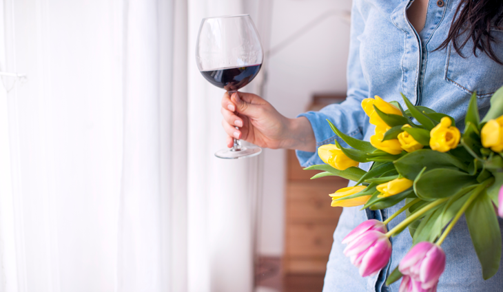 Woman holding wine and flowers