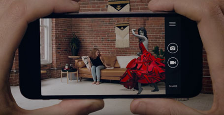 Mobile phone displaying augmented reality experience with woman in red