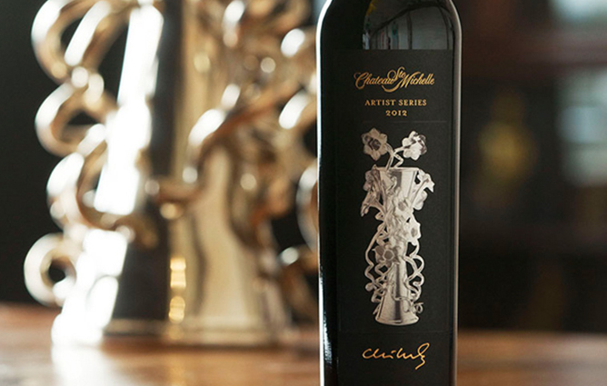 Chateau Ste Michelle's Artist Series bottle in front of the silver vase sculpture featured on the label