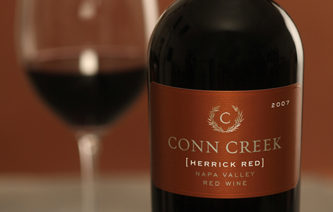 A close up shot on Conn Creek's 2007 Herrick Red label, standing in the foreground of a out of focus glass of wine.