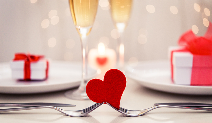 Two forks holding a felt heart in front of champagne glasses
