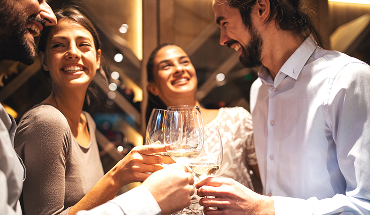 people smiling and clinking wine glasses