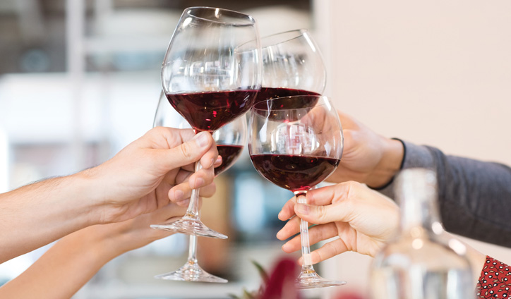 Hands clinking red wine glasses