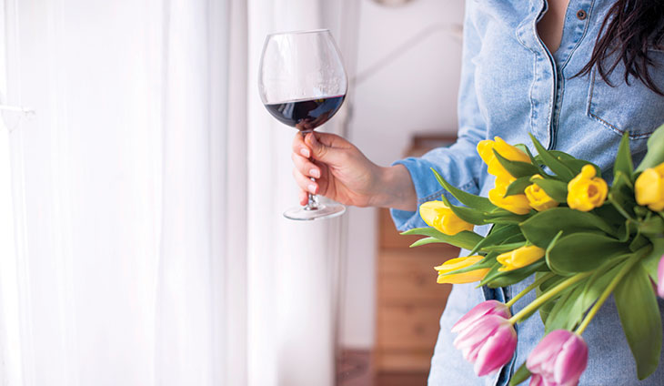 Woman holding tulips and a glass of wine