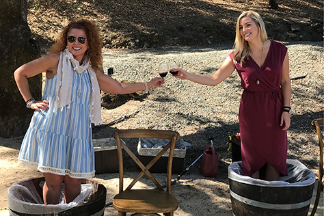Two women stomping grapes and clinking glasses