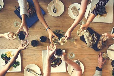 People clinking wine glasses over a table with food.