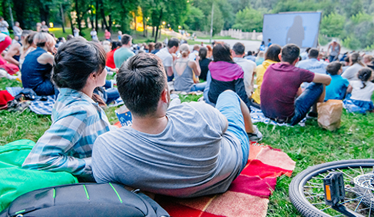 A couple sitting on a blanket watching an outdoor movie