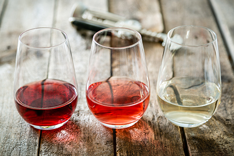 Red, white and rosé wine in wine glasses.