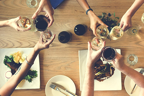 clinking wine glasses over a table with food.
